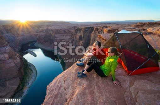 A couple camps on a ledge high above the Colorado and watches the sunset. Sunstar is real.