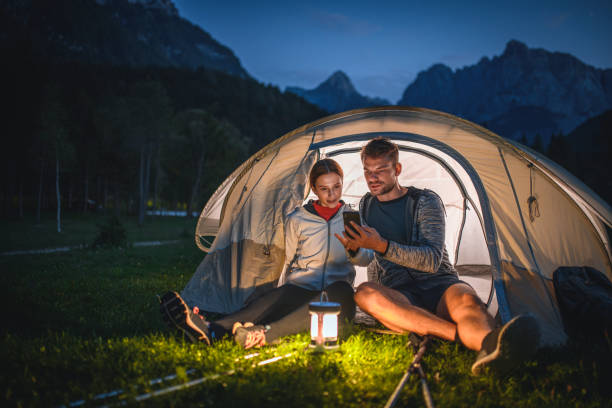 Camping Couple Checking Smart Phone at Dusk in Kranjska Gora stock photo