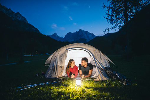 Relaxed couple in 20s and 30s lying on tent porch and smiling as they admire twilight view of scenic beauty in northwestern Slovenia.