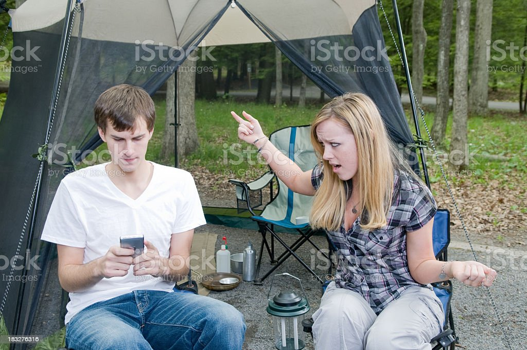 Camping couple, one animated, the other staring at a phone stock photo