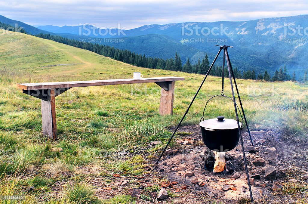 Camping fire and tourists bowler with food stock photo