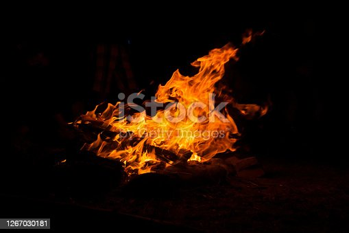 Camping fire in total darkness during night and nobody around