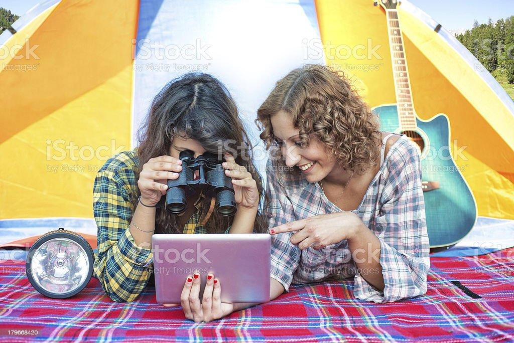 Camping: Friends Looking Tablet with Binoculars in a Tent royalty-free stock photo