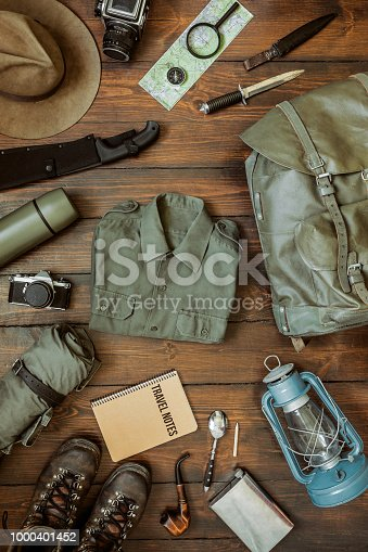 Camping gear including knife, clothes, boots, lantern, camera, hat, map, compass. Vertical wanderlust, safari postcard, poster, banner.