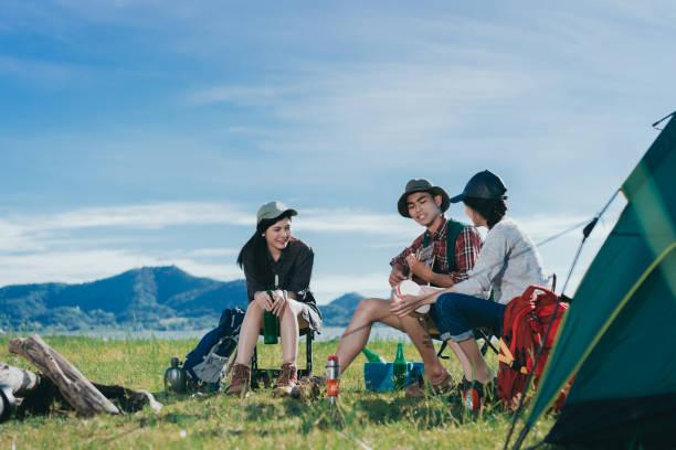 nhóm bạn cắm trại người châu á cùng nhau, thanh thiếu niên đi du lịch với ba lô, lều người đàn ông chơi guitar bài hát thư giãn trong kỳ nghỉ lễ ngồi trên ghế gần sông và núi xem. - friendship hình ảnh sẵn có, bức ảnh & hình ảnh trả phí bản quyền một lần