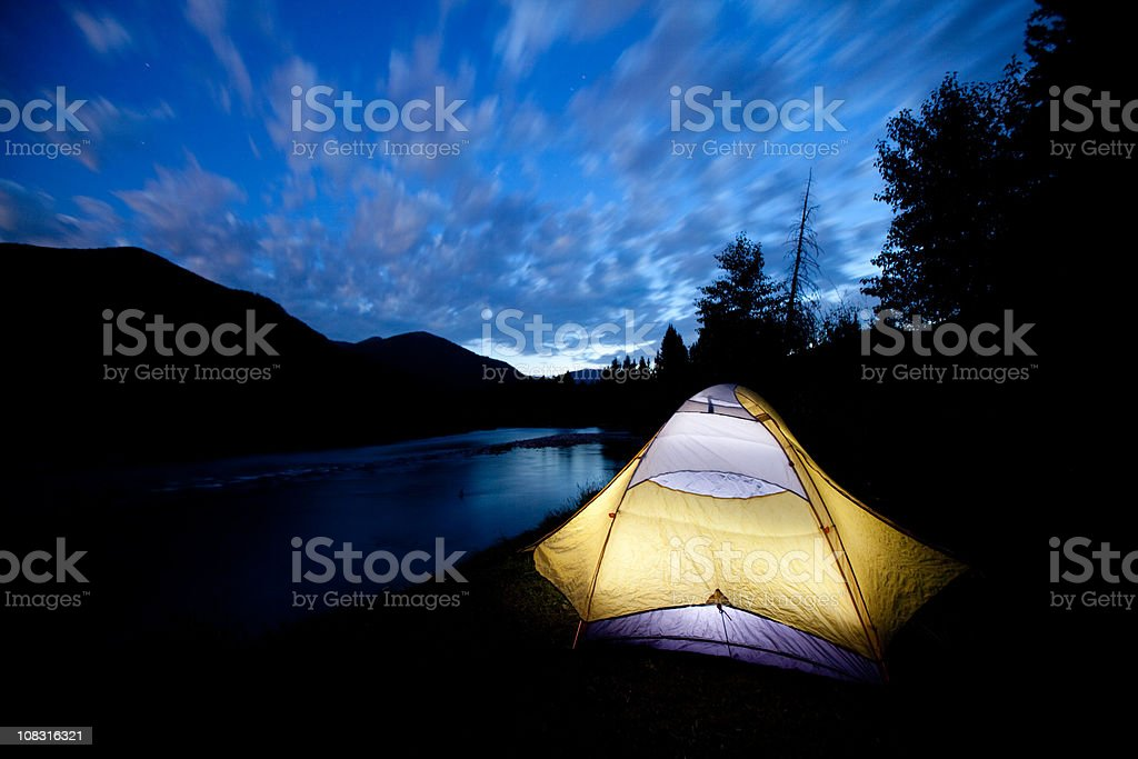 Camping in a tent by river at dusk royalty-free stock photo