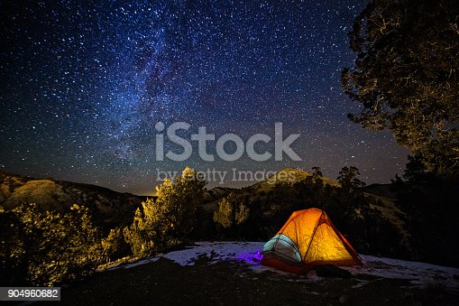 Camping in a Tent Under the Stars and Milky Way Galaxy - Scenic landscape with hils and mountains with orange glowing tent in dark with view of night sky with Milky Way and bright stars.