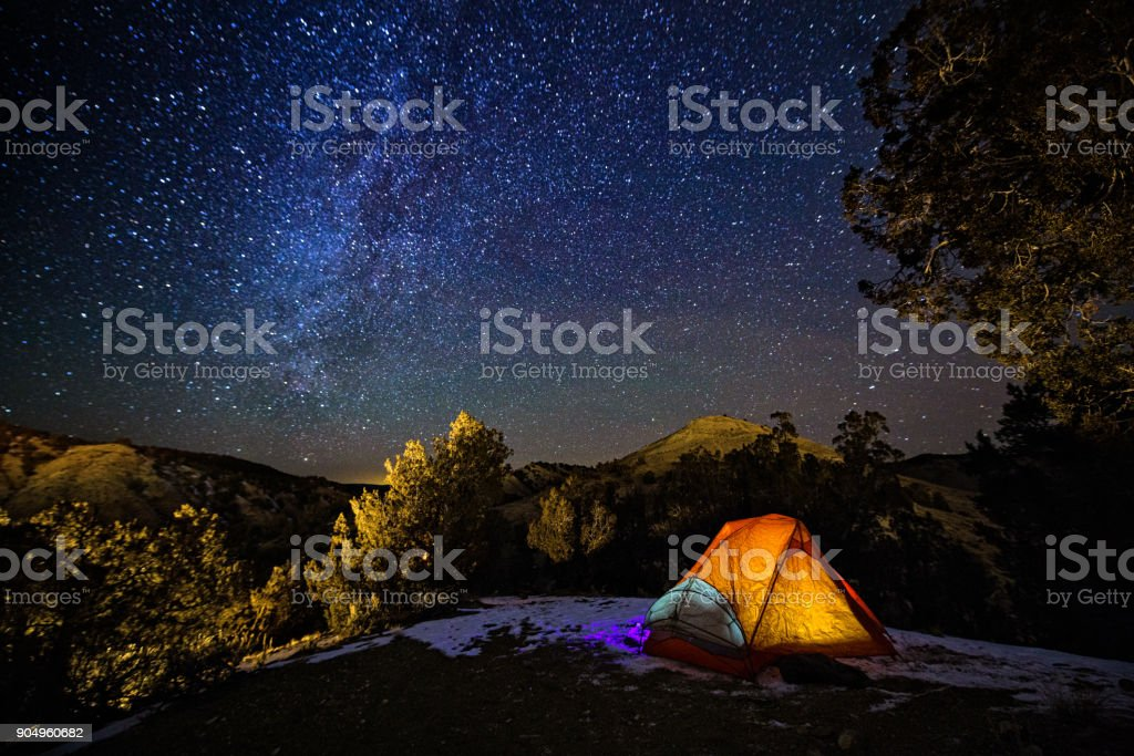 Camping in a Tent Under the Stars and Milky Way Galaxy stock photo