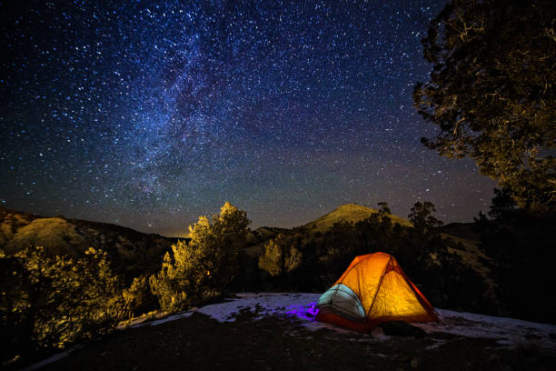 camping in a tent under the stars and milky way galaxy - camping stock photos and pictures