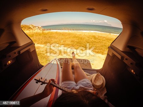Photo of young woman, camping in the back of her van and enjoying the sea view