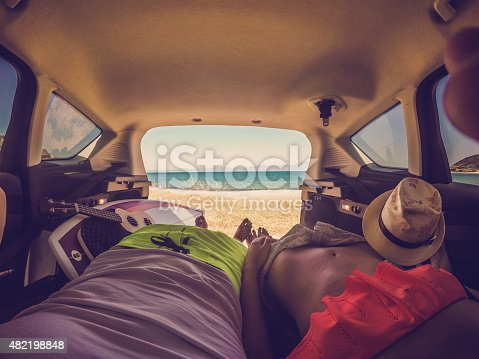 Photo of a friends enjoying the sea view from the trunk of their van
