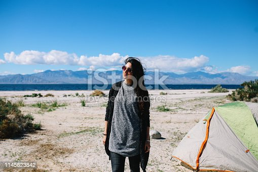 Young woman camping in tent by the Salton Sea - lake in Southern California, near Coachella Valley. She is wearing modern, laid back clothing, enjoying the morning sun.