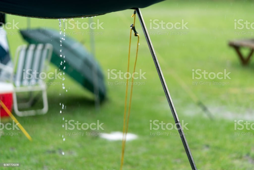 Water runs off a tent awning during rain