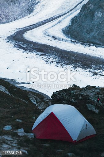 View of red tent, huge glacier and beautiful mountains during sunset in Switzerland
