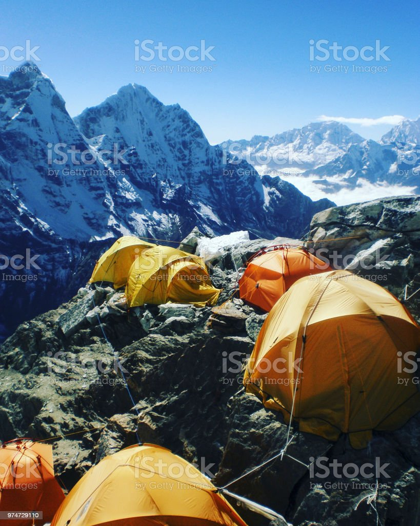 Camping near North Annapurna Base Camp overlooking Annapurna glacier. Outdoor camping scenery with snowy range in Himalayas. Camping outdoor on dramatic mountains background. stock photo