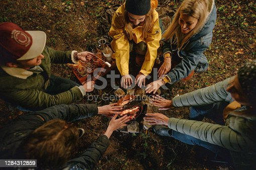 High angle view of a small group of friends warming up their hands over the campfire; friends camping in the woods and having a great time.