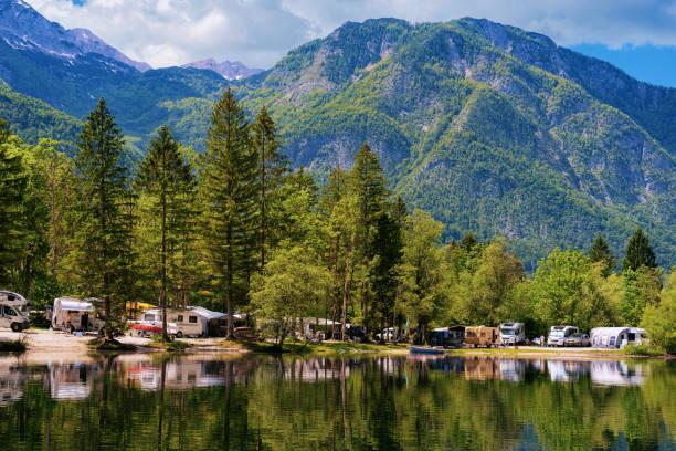 Camping of RV caravan trailers near Bohinj Lake in Slovenia stock photo
