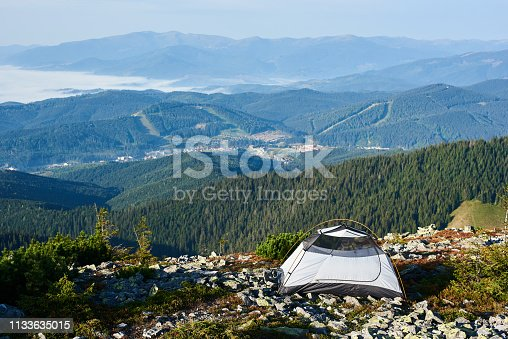 Camping on the top of mountain. White tourist tent on rocky hill in the morning. On background foggy mountains and small town in the valley. Tourism travel active lifestyle concept