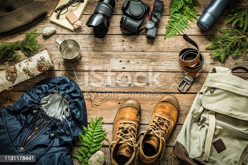 Camping or adventure trip scenery concept. Backpack, jacket, boots, belt, thermos and camera on wooden background captured from above (flat lay). Layout with free text (copy) space.