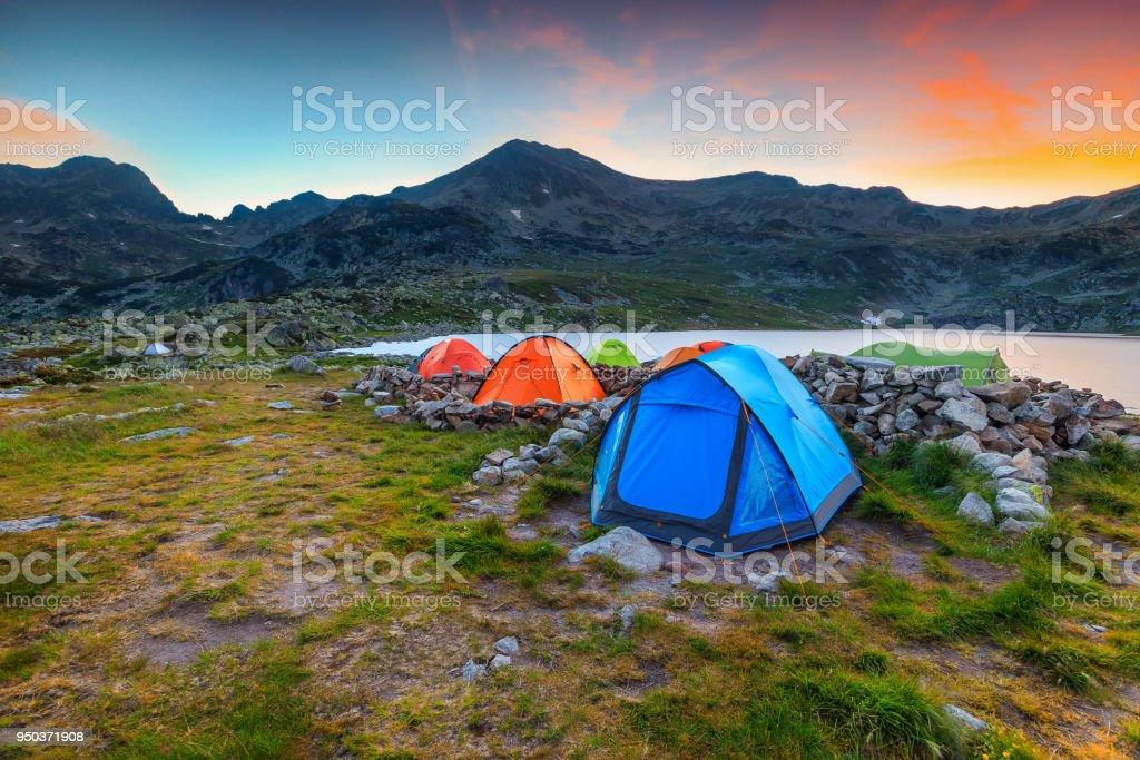 Camping place near alpine lake at sunset, Retezat mountains, Romania stock photo