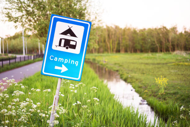 Camping sign in a countryside with a little river and green grass on background. stock photo