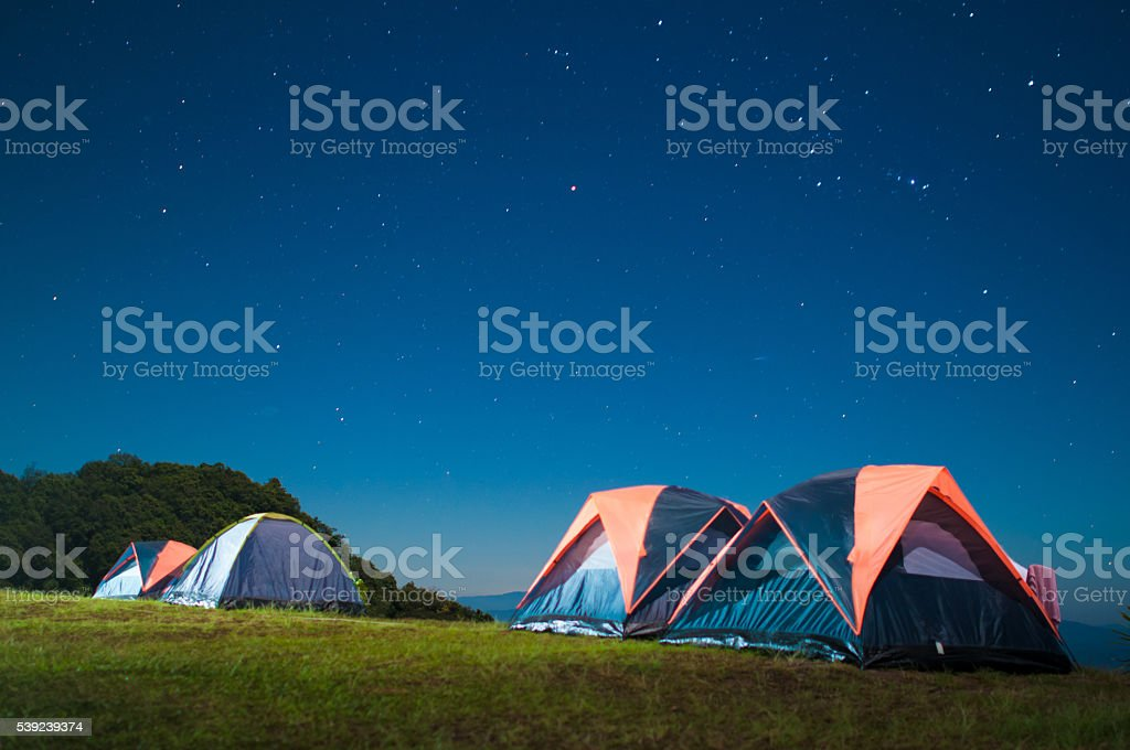Camping tent glows under a night sky full of stars. royalty-free stock photo