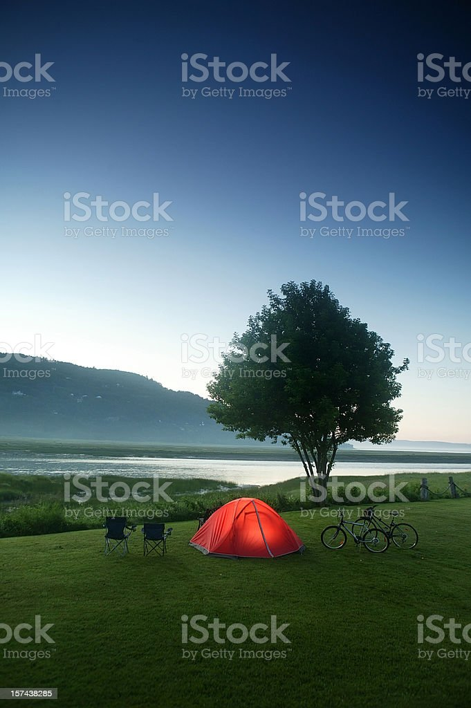 camping tent nearby river and mountain at dusk royalty-free stock photo