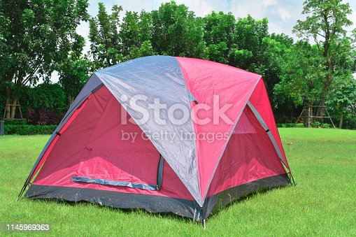 Camping tent on green grass and trees behind.