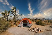 istock camping tent set up in desert landscape next to fire pit 1273217208