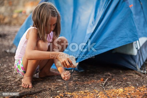 Little girl preparing and setting up tent for camping.  She wears casual summer clothes. Camp is located in forest with nice shade, but sun at sunset makes color vibrant and warm