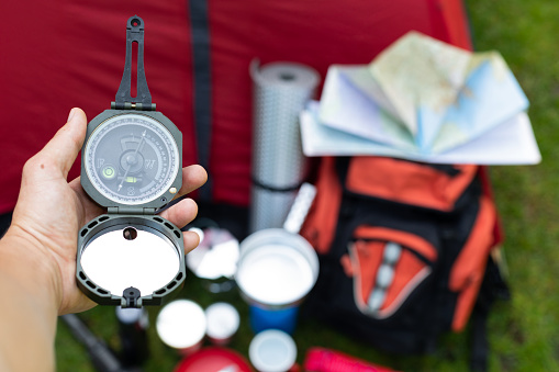 Picture of camping tools on the grass - backpack, tent, gas tank, cans, compass, etc - ready to go in the woods