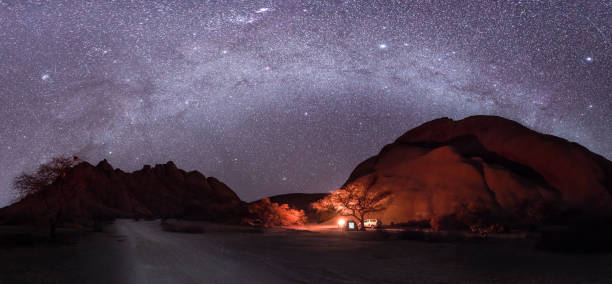 Camping under the milky way stars with a camp fire in Spitzkoppe, Namibia stock photo