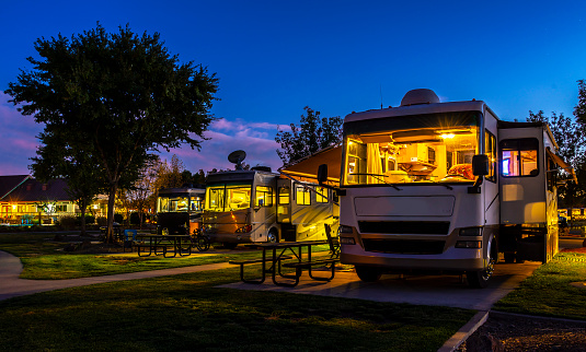 Rving at a resort in the evening lighted sky with class A rigs interior lights on