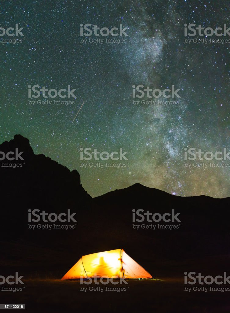 Red tent in the mountains under the stars and milky way.