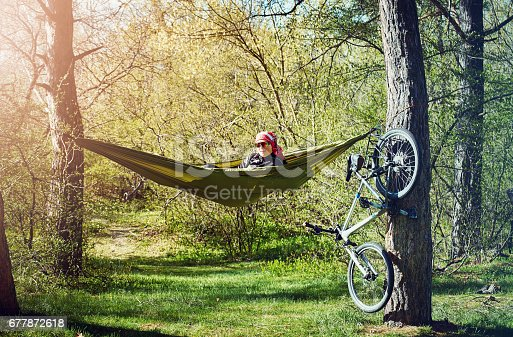 Rest in a hammock after a cycling adventure in the forest.