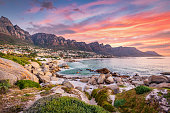 Beautiful sunset twilight view to Camps Bay, Scenic view during colorful sunset with beautiful cloudscape. Camps Bay the famous suburb of the city of Cape Town with white sandy beaches underneath the Table Mountain. Camps Bay, Cape Town, South Africa, Africa
