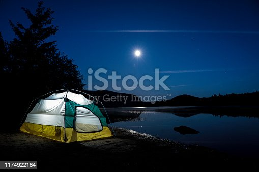 Campsite, tent close to lake at night. You can see the reflection of the moon on the lake. There is a light in the tent. Mont-Tremblant, Quebec, Canada