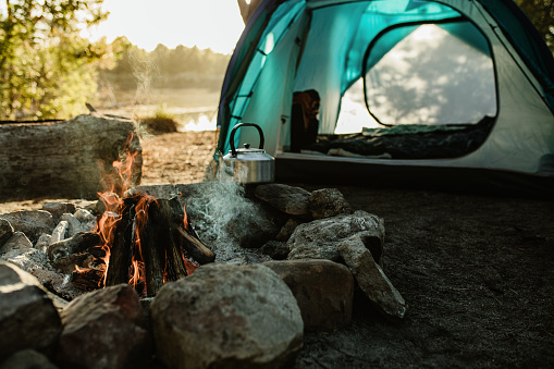 Campsite with a tent, kettle and burning fire pit in countryside. Camping by a lake in forest.