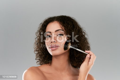 Studio shot of a beautiful young woman using a make up brush against a gray background
