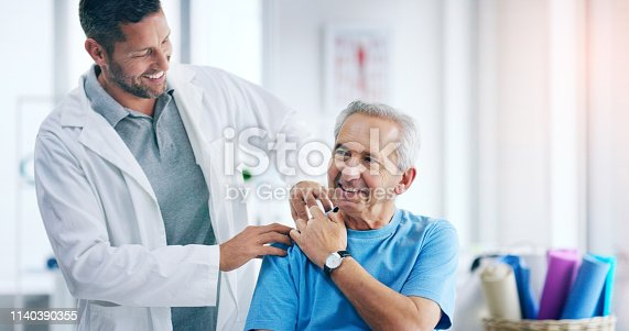 Shot of a male doctor doing some physiotherapy with a senior patient