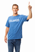 Portrait of handsome young man in a blue volunteer t-shirt with hand raised. Vertical shot. Isolated on white.