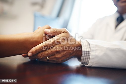 Closeup shot of an unrecognizable doctor holding a patient's hand in comfort