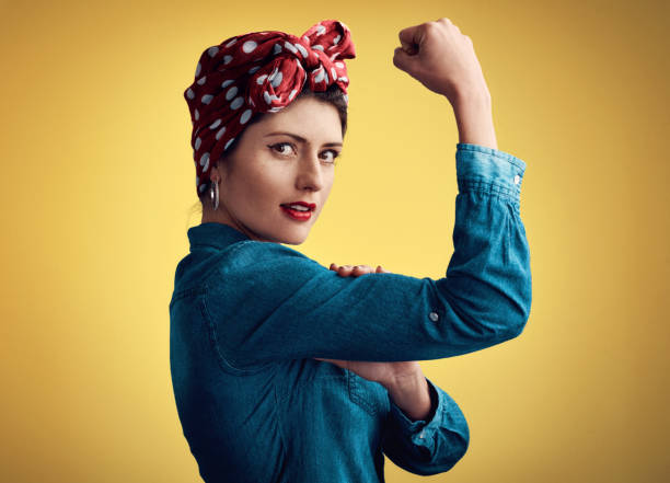 I can do it all Studio portrait of an attractive young woman flexing her bicep while standing against a yellow background women's rights stock pictures, royalty-free photos & images