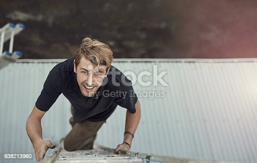 High angle portrait of a handsome young man climbing a ladder outside