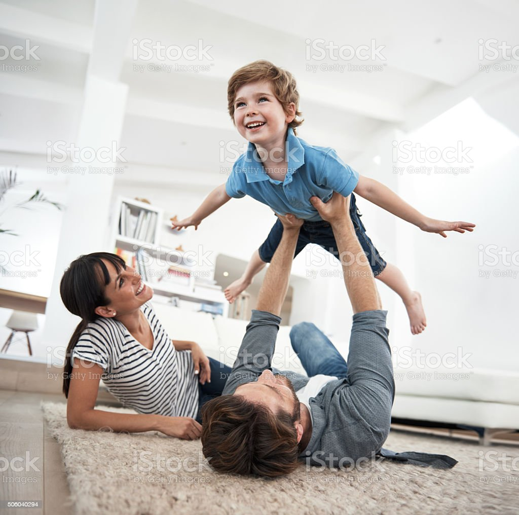 Shot of a mother and father playing with their son at...