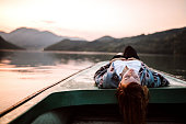 Woman lying on back on boat on the river with closed eyes