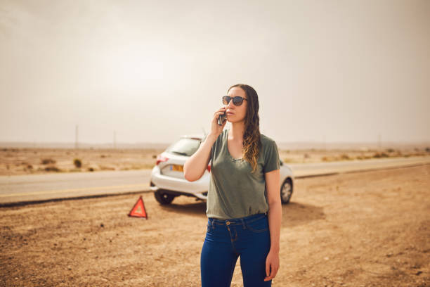 Can I get somebody to pick me up please? Shot of a young woman standing next to her broken down vehicle and using a smartphone aground stock pictures, royalty-free photos & images
