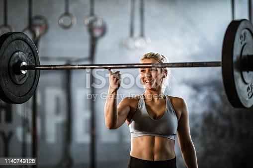 Happy athletic woman holding barbell on her index finger in a health club.