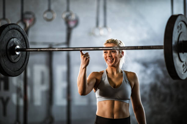 I can lift this barbell with my finger! Happy athletic woman holding barbell on her index finger in a health club. effortless stock pictures, royalty-free photos & images