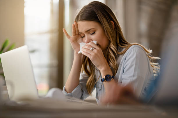 I can not believe I caught a cold! Young businesswoman with clpd and flu virus blowing nose while working in the office. allergy stock pictures, royalty-free photos & images